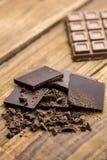 Dunkelheit und Milchschokolade auf einem Holztisch Lizenzfreies Stockbild