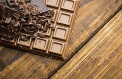 Dunkelheit und Milchschokolade auf einem Holztisch Lizenzfreie Stockfotografie
