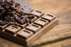 Dunkelheit und Milchschokolade auf einem Holztisch Stockfotos