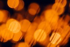 Dunkelorangefarbige Kreise Bokeh und Schattengräser auf schwarzem Hintergrund lizenzfreie stockfotos