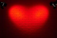 Dunkelrote Backsteinmauer mit Lichteffekt der Herzform und Schatten, abstraktes Hintergrundfoto, lichttechnische Ausrüstung Stockfoto