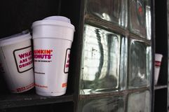 Dunkin Donuts cups disposed of on shelf outside train station Royalty Free Stock Photography