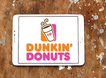Dunkin donuts logo. Logo of donut company and coffeehouse chain dunkin donuts on samsung tablet on wooden background Stock Photos