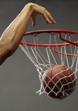 Dunking a basketball. A man dunking a basketball through a net with one hand Royalty Free Stock Image