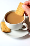 Dunking biscuit into tea Royalty Free Stock Photo