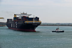 DUNKIRK/FRANCE - April 17, 2014: Tugboat towing the MSC Capella. Tugboat towing the MSC Capella container ship in the Dunkirk harbor Stock Photo