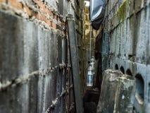 Dunkle alte Gasse umgeben mit alter Betonmauer Lizenzfreie Stockbilder