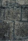 Dunkle alte Steinwand für Beschaffenheit oder Hintergrund, Schmutzart Lizenzfreie Stockbilder