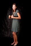 Dunkle behaarte Mädchenstellung färbte Kleid auf Schwarzem Lizenzfreies Stockfoto