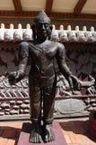 Dunkle buddhistische Skulptur in der Sonne Stockbilder