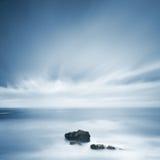 Dunkle Felsen in einem blauen Ozean unter bewölktem Himmel in einem falschen Wetter. Stockfoto