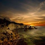 Dunkle Felsen- und Seeküste Stockbilder