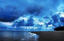 Dunkle gefährliche tropische Sturmwolken, die im Himmel über Ozeanküstenstrand rollen Stockbild