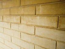 Dunkle gelbe Backsteinmauer und hellgelb Lizenzfreies Stockfoto