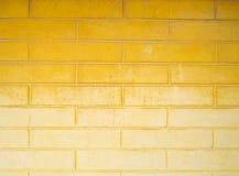 Dunkle gelbe Backsteinmauer und hellgelb Lizenzfreie Stockfotografie
