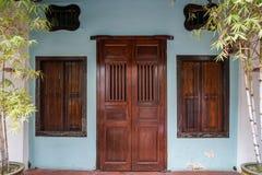 Dunkle hölzerne Einstiegstür und Fenster der Reihenhaus-Fassadenhintergrundshow mit Stahlstange auf hellblauer Wand mit Bambusblu lizenzfreies stockbild