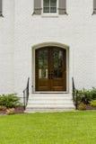 Dunkle hölzerne Haustür mit einem kleinen Bogen und schwarze Schienen mit grünem Gras Stockbild