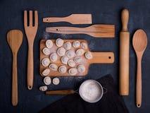 Dunkle hölzerne Küche der Draufsicht russischer Ravioli Dumplinga, die Kunsttabellenmehl kocht stockfoto