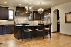 Dunkle hölzerne Küche mit Granit-Zählwerken Lizenzfreie Stockbilder