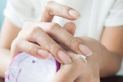 Dunkle Hautfrau, die Creme an Hand weiß werden, Schönheitskonzept zutrifft Stockbilder