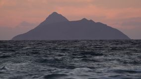 Dunkle Insel und Wellen an der Dämmerung stock video
