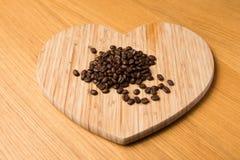 Dunkle Kaffeebohnen auf Herz geformtem hackendem Brett Stockbilder