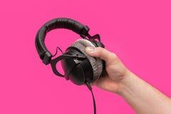 Dunkle Kopfhörer in der Hand Stockfoto