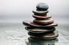 Dunkle oder schwarze Felsen auf Wasser, Hintergrund für Badekurort, entspannen sich oder Wellnesstherapie Lizenzfreie Stockbilder