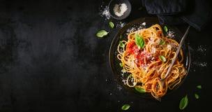 Dunkle Platte mit italienischen Spaghettis auf Dunkelheit stockbild