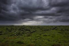Dunkle Regenwolken über einem Moos bedeckten Lava Field Lizenzfreie Stockfotografie