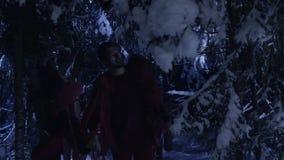 Dunkle Schattenbilder des Mannes und der Frau, die in Wald des verschneiten Winters nachts stilles umziehen stock video footage