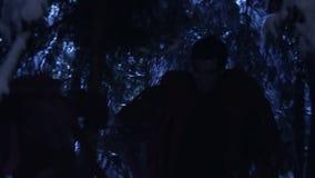 Dunkle Schattenbilder von zwei Leuten, die in Wald des verschneiten Winters nachts stilles gehen stock video footage