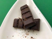 Dunkle Schokolade auf einer weißen Platte lokalisiert auf grünem Hintergrund lizenzfreie stockfotos