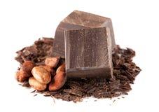 Dunkle Schokolade und Kakaobohnen über Weiß Lizenzfreie Stockfotografie