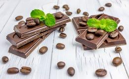 Dunkle Schokolade verziert mit Kaffeebohnen und Minze Lizenzfreie Stockbilder