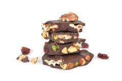 Dunkle Schokoladenbarke mit Mischnüssen auf weißem Hintergrund Stockfotografie