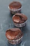 Dunkle Schokoladenmuffins auf dunklem Schiefer Stockbilder