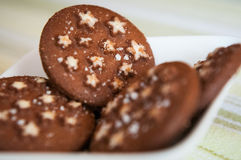 Dunkle Schokoladenplätzchen des Weihnachtsfeiertags mit weißen Sternen Lizenzfreie Stockbilder