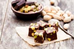 Dunkle Schokoladenwürfel mit Pistazien auf hölzernem Hintergrund Stockfoto