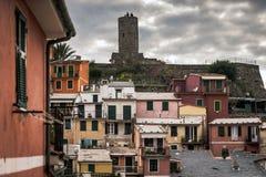 Dunkle Stadt von Vernazza mit Leuten auf Ruinen eines alten Turms auf einem Hintergrund Stockfotos