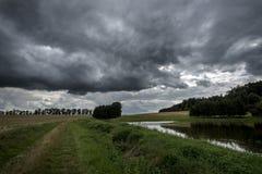 Dunkle Sturmwolken über einem Teich zwischen Feldern am Wald in Böhmen Lizenzfreies Stockbild