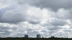 Dunkle Sturmwolken laufen in Himmel über städtischem Gebäude und Wald stock video