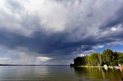 Dunkle Sturmwolken vor Regen über dem See Stockbild
