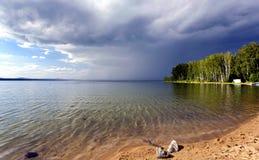 Dunkle Sturmwolken vor Regen über dem See Lizenzfreies Stockfoto