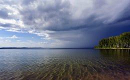Dunkle Sturmwolken vor Regen über dem See Stockfoto