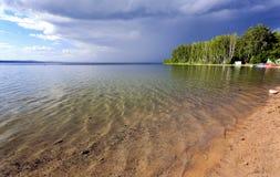 Dunkle Sturmwolken vor Regen über dem See Stockbilder