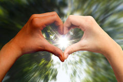 Dunkle und helle Hauthände im Herzen formen Stockfotos