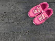 Dunkle Weinlese schöner rosa Frauen ` s Laufschuhe auf dem Boden Die Ansicht von der Oberseite stockbild
