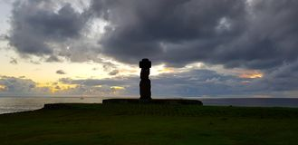 Dunkle Wolken über einem moai bei Sonnenuntergang, Hanga Roa, Osterinsel, Chile stockfoto