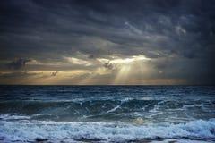 Dunkle Wolken über stürmisches Seeversteckendem Sonnenlicht in Thailand Stockbild